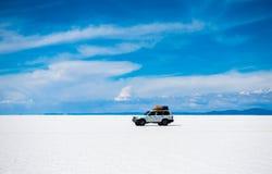 Zonneschijnlandschap van Salar de Uyuni in Bolivië en auto stock foto