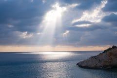 Zonnestraal die de wolken doordringen bij zonsondergang die oceaanw ilumminating royalty-vrije stock fotografie