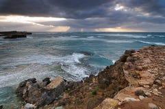 Zonnestraal die donkere wolk breken bij kust Royalty-vrije Stock Foto's