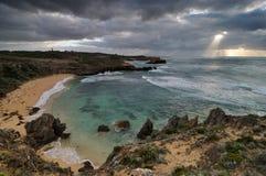 Zonnestraal die donkere wolk breken bij kust Royalty-vrije Stock Foto