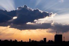 Zonnestraal door de dramatische wolk tijdens zonsondergangtijd, met silh stock afbeelding