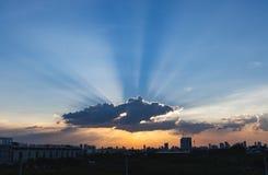 Zonnestraal door de dramatische wolk tijdens zonsondergangtijd, met de silhueetebouw op achtergrond stock afbeeldingen