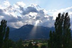 Zonnestraal door wolken in de Franse Alpen stock foto