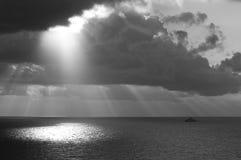 Zonnestraal door wolken die op oceaan glanzen royalty-vrije stock afbeelding