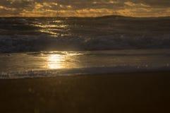 Zonnestraal op een schuimgolf op de kust royalty-vrije stock afbeelding