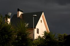 Zonnestraal op huis vóór het onweer stock fotografie