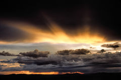 Zonnestraal over onweer stock foto's