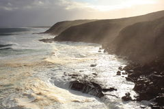 Zonnestraal over rollende golven op rotsachtige kust royalty-vrije stock foto's