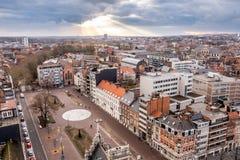 Zonnestralen die door het wolkendek breken, met een panorama van Leuven, Vlaanderen, België stock foto