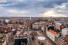 Zonnestralen die door het wolkendek breken, met een panorama van Leuven, Vlaanderen, België stock afbeelding