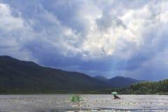 Zonnestralen die door onweerswolken over bergmeer breken Stock Foto