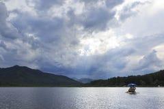 Zonnestralen die door onweerswolken over bergmeer breken Stock Foto's