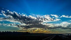 Zonnestralen die hun licht op de blauwe hemel ontwerpen Stock Fotografie