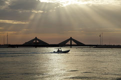 Zonnestralen en de verzendende boot dichtbij Sheikh Salman Causeway-brug Bahrein royalty-vrije stock afbeeldingen