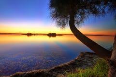 Zonnestralen in het water bij zonsondergang worden weerspiegeld die stock foto's