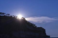 Zonnestralen met bomen, rotsen en wolken Royalty-vrije Stock Foto