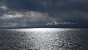 Zonnestralen over het water in de regen Stock Afbeelding