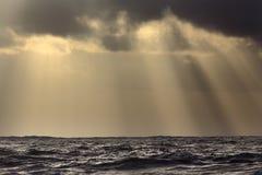 Zonnestralen over overzees stock foto