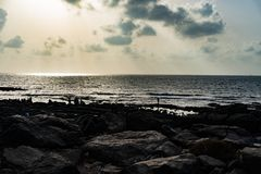 Zonnestralen van de wolken en een rotsachtig strand stock afbeeldingen