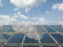 Zonnewarmtepaneel op blauwe hemel en wolkenachtergrond Het zonnewarmtepaneel voor bereidt warm water voor stock foto