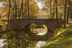 Zonnig de herfstlandschap - een park in gouden kleuren, een waterweg met schilderachtige brug, vergeelde bladeren overheerst in h royalty-vrije stock foto