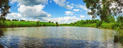 Zonnig de zomer winderig landschap met rivier en mooie wolken in blauwe hemel royalty-vrije stock fotografie