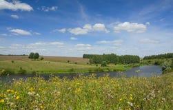 Zonnig de zomerlandschap met rivier, gebieden, groene heuvels en mooie wolken in blauwe hemel royalty-vrije stock afbeelding
