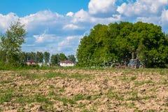 Zonnig landschap van het platteland in het begin van de zomer Een tractor ploegt het gebied Stock Afbeelding