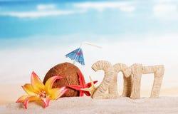 Zonnig strand met een kokosnoot van inschrijvings 2017 Kerstmis en zeester op overzees Stock Fotografie