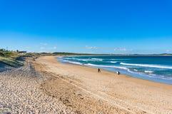 Zonnig strand met twee unrecognisable surfers stock afbeelding