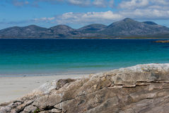 Zonnig strand met zandduinen, lang gras en blauwe hemel Stock Foto