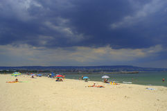 Zonnig strand tegen donkere hemel Royalty-vrije Stock Foto