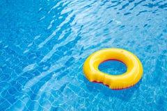 Zonnige dag bij de pool Heldere gele vlotter in blauw zwembad, royalty-vrije stock foto's