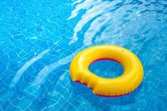 Zonnige dag bij de pool Heldere gele vlotter in blauw zwembad, stock afbeeldingen