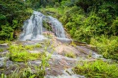 Zonnige dag op het gebied met glashelder water en waterval royalty-vrije stock foto