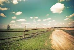 Zonnige dag in platteland Lege landelijke weg bij de zomer Royalty-vrije Stock Afbeeldingen