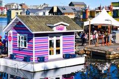 Zonnige dag voor toeristen onder drijvende winkels, huizen en restaurants in Victoria Inner Harbour, Fishermans-Werf, Canada royalty-vrije stock foto