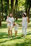 Zonnige de zomerdag De gelukkige jonge familie kleedde zich in de witte vrijetijdskledingsgangen in het park royalty-vrije stock foto's