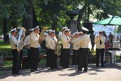 Zonnige de zomerdag in het stadspark fanfarekorps van zeelieden in het stadspark dat wordt gespeeld stock fotografie