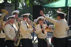 Zonnige de zomerdag in het stadspark fanfarekorps van zeelieden in het stadspark dat wordt gespeeld stock foto