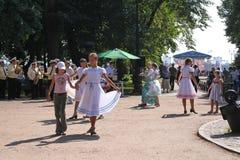 Zonnige de zomerdag in het stadspark meisjes openbare entertainers die met de toeristenmensen onder de muziek van een militair me Royalty-vrije Stock Foto