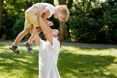 Zonnige de zomerdag De vrolijke vader hief zijn kleine zoon boven zich op en kietelend hem stock afbeelding