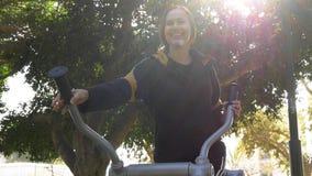 Zonnige glimlachende die vrouw op apparaten om op te leiden in werking wordt gesteld stock foto's