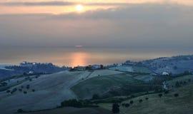 Zonnige heuvel bij dageraad met geïsoleerde olijfbomen en sommige landbouwbedrijven dichtbij het Adriatische overzees royalty-vrije stock afbeeldingen