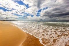 Zonnige oceaanoever met zand en golven Royalty-vrije Stock Fotografie