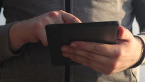 Zonnige tablet in de handen van de kerel op de aard stock footage