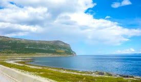 Zonnige wegvoorwaarden in Noorwegen met bergen stock fotografie