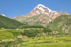 Zonovergoten berg Kazbek op blauwe hemelachtergrond Royalty-vrije Stock Fotografie
