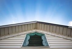Zonovergoten stralen die achter een hoogtepunt bereikt dak met rustiek blauw venster glanzen stock afbeelding