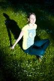 Zonovergoten vrouw in schaduwrijk park stock foto's